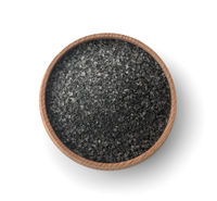 Top view of black salt in wooden bowl