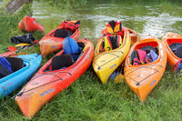 eight kayaks on the shore of the river, colorful kayaks at the pond
