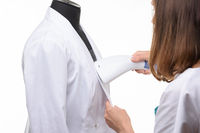 Girl handles medical clothing by steamer on a white background