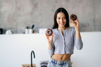 Portrait of rejoicing woman holding tasty donut at home