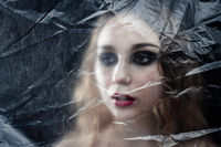 Young beauty sad woman trapped behind a plastic sheet as protection against COVID-19. Nicely fits fo