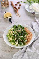 Gluten-free green vegetarian salad made of microgreen sprouts peas, avocado, quinoa, spinach, season