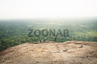 Tourists sitting on Pidurangala Rock during sunset and backlight in Sigiriya, Sri Lanka