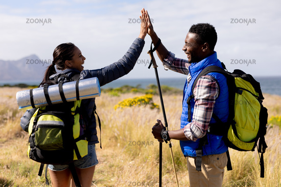 Fit african american couple wearing backpacks high fiving nordic walking on coast
