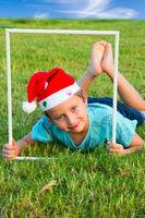 Boy in a clownish cap of Santa Claus