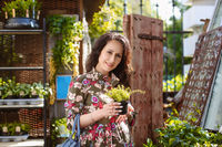 Woman shopping for flowers in garden centre variation of plants