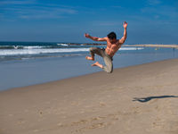 Excited shirtless young man jumping on beach