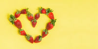 Strawberry heart on a yellow background. Fresh strawberries closeup. Valentine's Day. Top view, copy space.