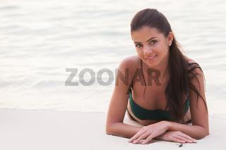 Smiling woman lying on beach