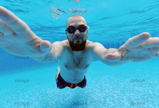 Middle aged man wear googles and swimming trunks submerged in water enjoy summer vacations swimming in pool. Active lifestyle and sport activity concept