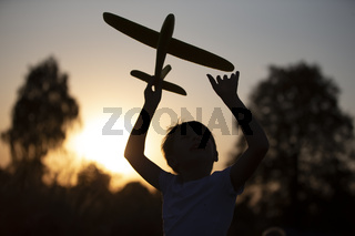Happy child plays with an airplane at sunset. Silhouette of a boy with an airplane on the background of the sun.