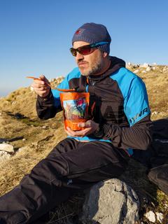 Bergsteiger ißt eine Trekkingmahlzeit