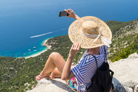Active sporty woman on summer vacations taking selfie picture while enjoying beautiful coastal view of Cres island, Croatia from Lubenice traditional costal village