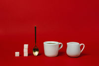 Cup of americano, golden spoon, creamer and sugars cups on red