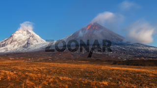 Autumn mountain landscape view at sunrise of eruption active volcano