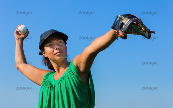 Woman with glove and cap throws baseball outdoors