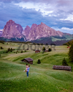 couple men and woman on vacation in the Dolomites Italy,Alpe di Siusi - Seiser Alm with Sassolungo - Langkofel mountain group in background at sunset. Yellow spring flowers and wooden chalets in Dolomites, Trentino Alto Adige, South Tyrol, Italy, Europe