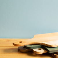 Wooden tray, cutting board, plate on wooden table with blue background