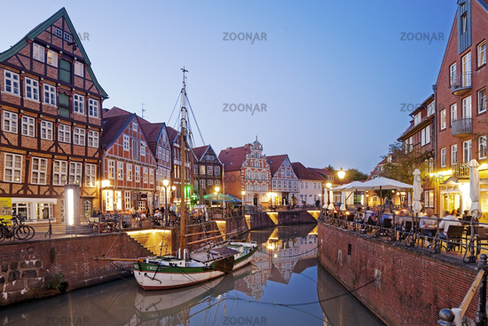 Historic houses at the Hanseatic harbor with the sailing ship Willi in the evening, Stade, Germany