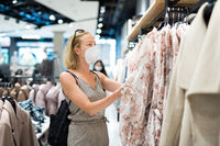 Fashionable woman wearing protective face mask shopping clothes in reopen retail shopping store. New normal lifestyle during corona virus pandemic
