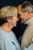close up portrait of old couple wife and husband smiling. Dark blue background. Happy lovers on retirement. Stop ageism.