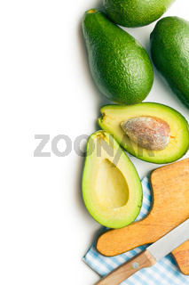 green avocados with knife and cutting board
