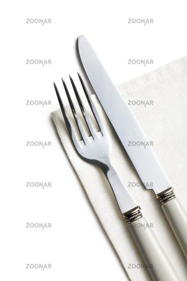 fork and knife on white napkin