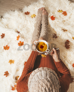 Woman holds a bowl of spiced pumpkin soup sitting on cozy rug