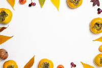 Autumn concept. Colorful dry leaves and sweet persimmon fruit, pumpkin on white background. flat lay, top view, copy space