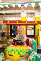 A very joyful and happy little blond boy of three years old is riding in a yellow car with a green car in the summer Riviera Amusement Park