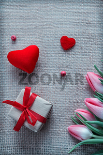 Valentine's day background with pink tulips and hearts.