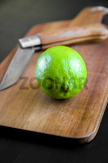 Lime and old traditional pocket knife on a cutting board