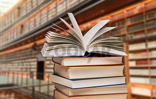 Bücherstapel vor Regalen einer Bibliothek