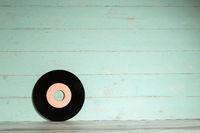 Vinyl record on vintage wooden background