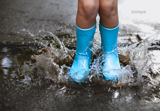 Child wearing blue rain boots jumping into a puddl