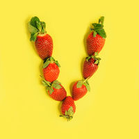 Letter L made from Strawberries on a yellow background. Fruit alphabet.