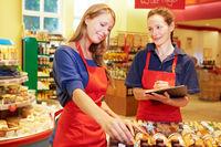Auszubildende hilft Marktleiterin im Supermarkt
