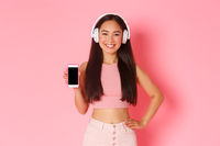 Technology, communication and online lifestyle concept. Smiling beautiful asian girl promote mobile phone application, showing smartphone screen while listening music in headphones