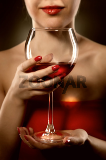 woman in red holding wine glass and smiles