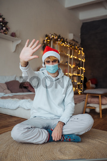 Caucasian guy in face mask and Santa Claus hat posing and looking at camera