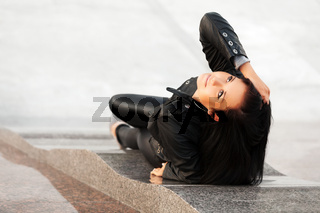 Happy young woman lying on the sidewalk