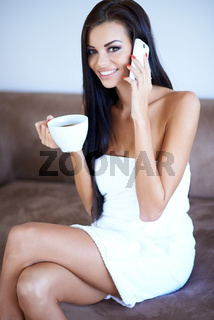 Woman drinking coffee and chatting on a mobile