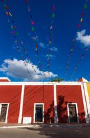 Vibrant flag chains over bright blue sky along red colonial building, Valladolid, Yucatan, Mexico