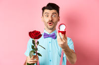 Valentines day. Funny man with moustache and bow-tie making proposal, showing engagement ring and propose with red rose, standing over pink background