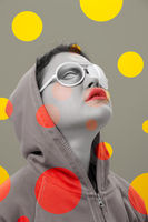 Art collage with alternative funky girl. Close up fashion portrait young beautiful woman in hoodie and white strange glasses with eye. Multi-colored circles. Unusual youth fashion concept.