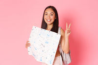 Travelling, lifestyle and tourism concept. Portrait of cheerful asian smiling girl tourist on vacation, wearing backpack, holding map and showing peace, kawaii gesture, explore city abroad, pink wall