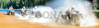 Four Men driving motocross ATV quad through splashing river lake water with high speed. Foy, Foyross Lake, Sudbury, Canada.
