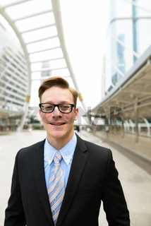 Happy young handsome blond businessman with eyeglasses in the city outdoors