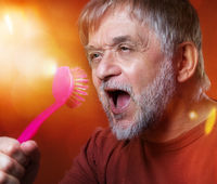 Crazy old man singing with kitchen brush and dreaming