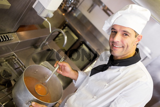 Smiling male chef preparing food in kitchen